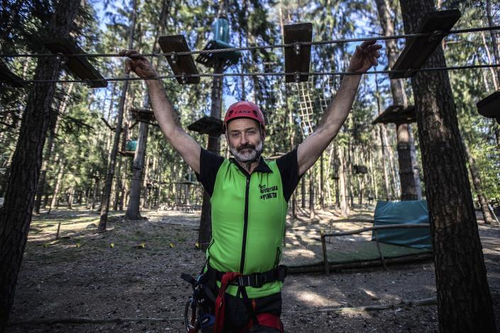 """In this image take on Thursday, April 23, 2020 Diego Fregona, 58, adventure park owner, poses inside the park, in Clusone, near Bergamo, northern Italy. Fregona spent all his savings to repair the damage done to his 10.000sqm park after a whirlwind in October knocked down trees, climbing ropes and suspended trails, only to remain closed with very little money and lots of doubts as to whether he'll ever be able to restart. His words for the Associated Press were """"There isn't a family who didn't have a bereavement, the only thing left to do is to get up again."""" (AP Photo/Luca Bruno)"""