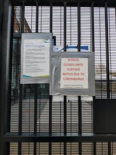 School gate with notices that the school is closed