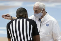 North Carolina head coach Roy Williams speaks with an official during the first half of an NCAA college basketball game against Florida State in Chapel Hill, N.C., Saturday, Feb. 27, 2021. (AP Photo/Gerry Broome)