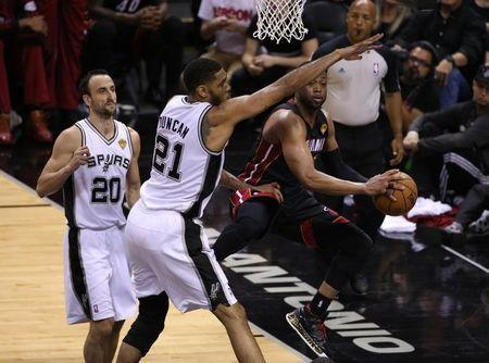 Dwyane Wade (3) passes off under the basket against San Antonio Spurs forward Tim Duncan (21) in game five of the 2014 NBA Finals at AT&T Center. Jun 15, 2014; San Antonio, TX, USA; Soobum Im-USA TODAY Sports