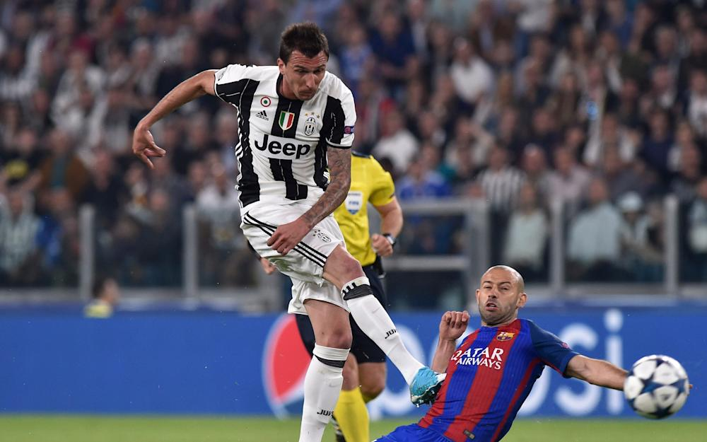 Barcelona's Javier Mascherano attempts to block a shot from Juventus' Mario Mandzukic - Credit: REUTERS