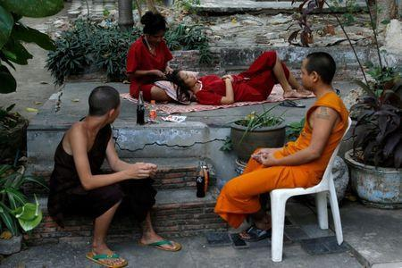 Nat (2nd L) combs a friend's hair during their stay at Wat Thamkrabok monastery in Saraburi province, Thailand, February 3, 2017. REUTERS/Jorge Silva