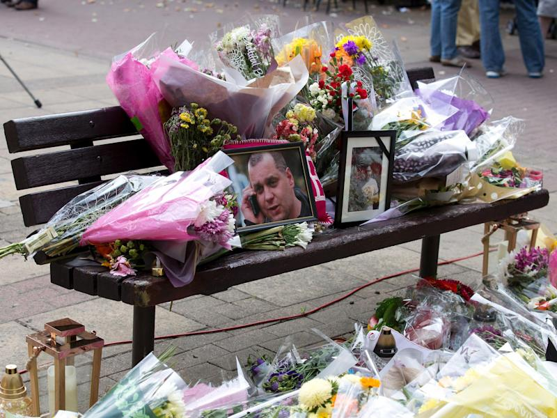 Floral tributes and a photograph of Arek Jozwik on a bench at the shopping centre in Harlow where he was killed