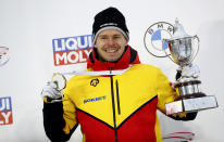 Germany's Christopher Grotheer holds the trophy on the podium after taking first place in the men's skeleton race at the Bobsleigh and Skeleton World Championships in Altenberg, Germany, Friday, Feb.12, 2021. (AP Photo/Matthias Schrader)