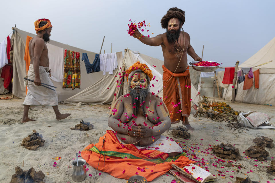A Hindu Holy man prays as others shower flower petals on him during Magh Mela festival, in Prayagraj, India. Tuesday, Feb. 16, 2021. Hindus believe that ritual bathing on auspicious days can cleanse them of all sins. A tented city for the religious leaders and the believers has come up at the sprawling festival site with mounted police personnel keeping a close watch on the activities. The festival is being held amid rising COVID-19 cases in some parts of India after months of a steady nationwide decline. (AP Photo/Rajesh Kumar Singh)