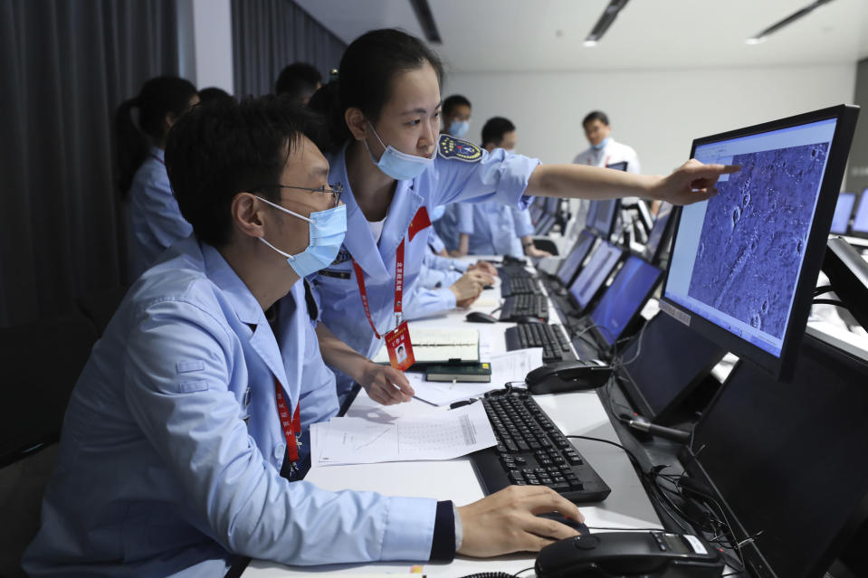 In this photo released by China's Xinhua News Agency, technicians work at the Beijing Aerospace Control Center in Beijing, Saturday, May 15, 2021. China landed a spacecraft on Mars for the first time on Saturday, a technically challenging feat more difficult than a moon landing, in the latest advance for its ambitious goals in space. (Jin Liwang/Xinhua via AP)