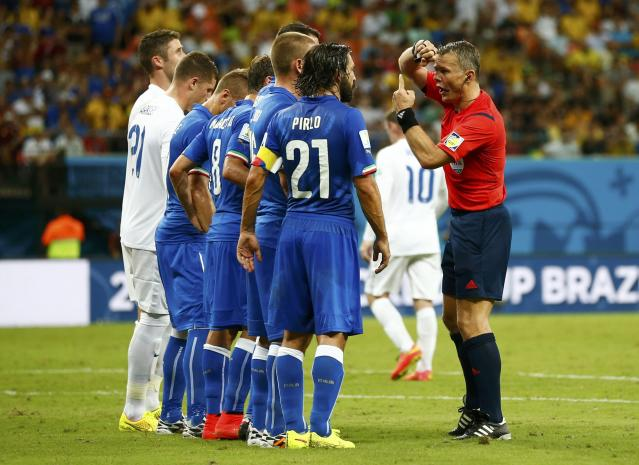 Referee Bjorn Kuipers talks to Italy's Andrea Pirlo during their 2014 World Cup Group D soccer match at the Amazonia arena in Manaus
