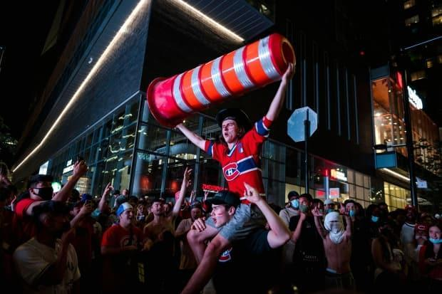 Montreal Canadiens fans raise a traffic cone in a victory celebration. (Andrej Ivanov / AFP via Getty Images - image credit)