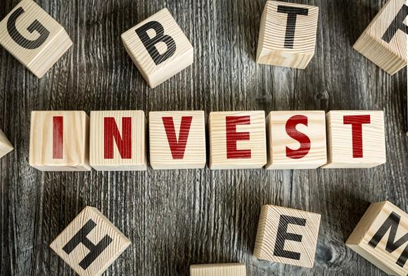 "The word ""invest"" spelled out in red on wood blocks."
