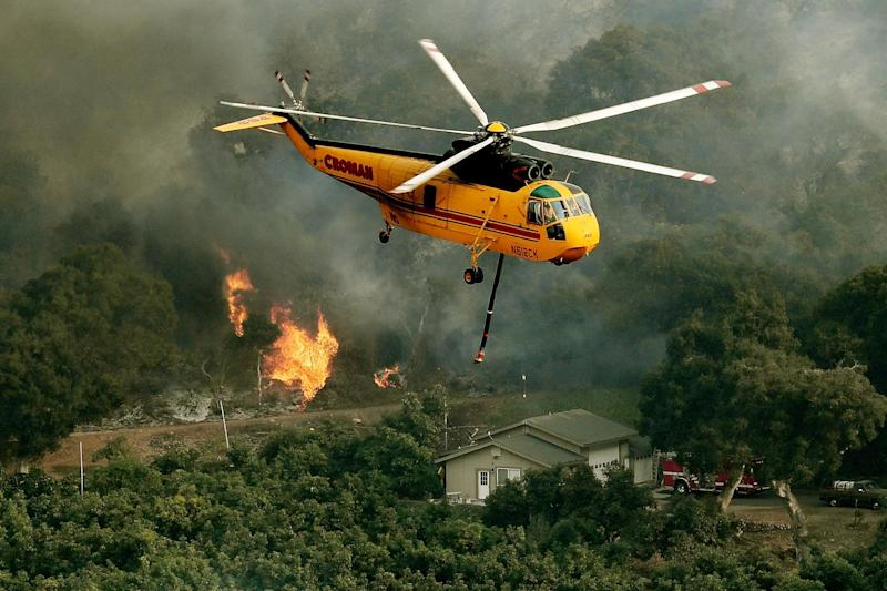 Huge blaze: A firefighting helicopter battles to contain flames: AFP