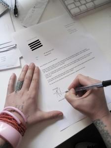 Tattooed and bangled hands writing a resignation letter