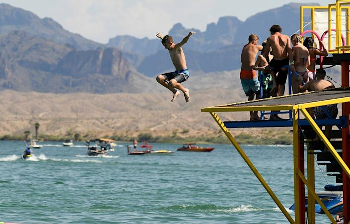 """A boy takes a leap on a hot day in Lake Havasu City, Ariz. The tourist town has been crowded by Californians over the last few weekends, and residents are concerned about the cornavirus spreading. <span class=""""copyright"""">(Wally Skalij / Los Angeles Times)</span>"""