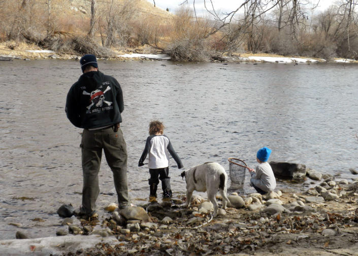 """This undated photo released courtesy Laura Bugni-Daniel shows her husband Carl with her sons Huckleberry, center and Maximus Trout, right with their dog Rabito on their farm onThe Big Hole river near Butt, Montana. Until she introduced """"magic cheese"""" to her sick and aging bulldog, Bugni-Daniel watched him suffer for two years. He'd spend his days lying down or throwing up. Today, at age 12, he plays like a puppy through the day, his fur is soft and he sleeps at night, soothed not by magic, but by the dose of marijuana in that cheese. Bugni-Daniel is part of a growing movement to give medical marijuana to pets in pain. (AP Photo/Courtesy Laura Bugni-Daniel)"""