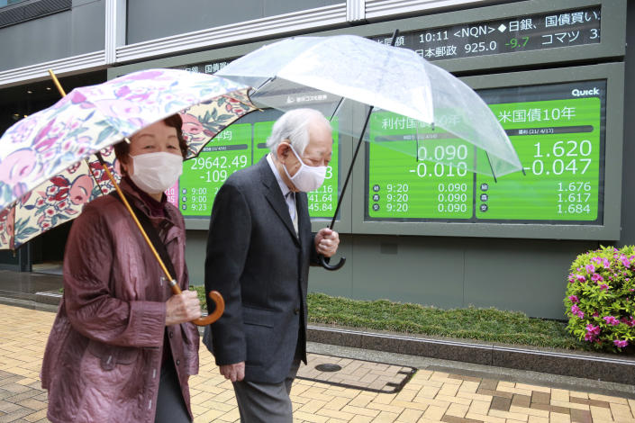 A couple wearing face masks walks by an electronic stock board of a securities firm in Tokyo, Wednesday, April 14, 2021. Asian stock markets rose Wednesday after Wall Street hit a high following an uptick in U.S. inflation and an order by regulators to suspend use of Johnson & Johnson's coronavirus vaccine. (AP Photo/Koji Sasahara)