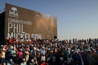 Congratulations: Fans sit in front of a leaderboard hailing Phil Mickelson's win at Kiawah Island