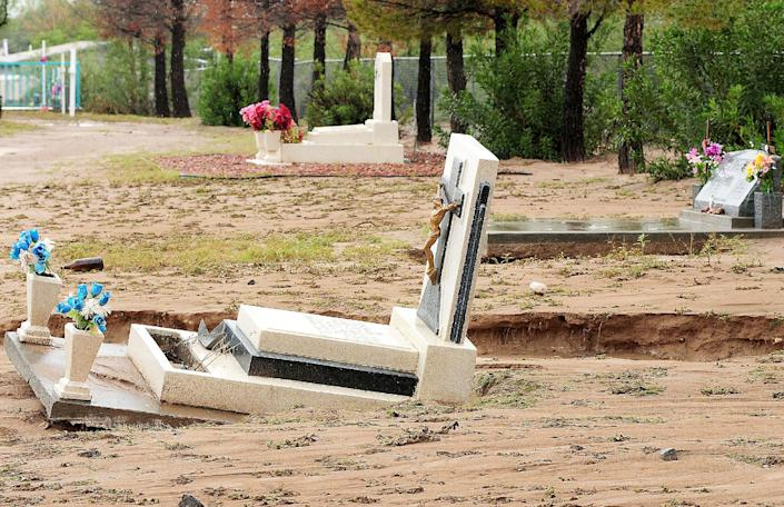 Graves at the La Union Cemetery in La Union, N.M. are damaged from Thursday's heavy flood waters Friday, Sept. 13, 2013. New Mexico was drenched Thursday by another round of record rainfall. (AP Photo/The Las Cruces Sun-News, Shari Vialpando-Hill) MANDATORY CREDIT