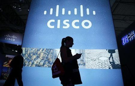A visitor walks past a Cisco advertising panel as she looks at her mobile phone at the Mobile World Congress in Barcelona