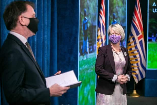 Provincial Health Officer Bonnie Henry smiles under her mask at B.C. Health Minister Adrian Dix during a Monday morning press conference announcing the province is on track to move into Step 2 Tuesday of a four-step reopening plan. (Mike McArthur/CBC - image credit)