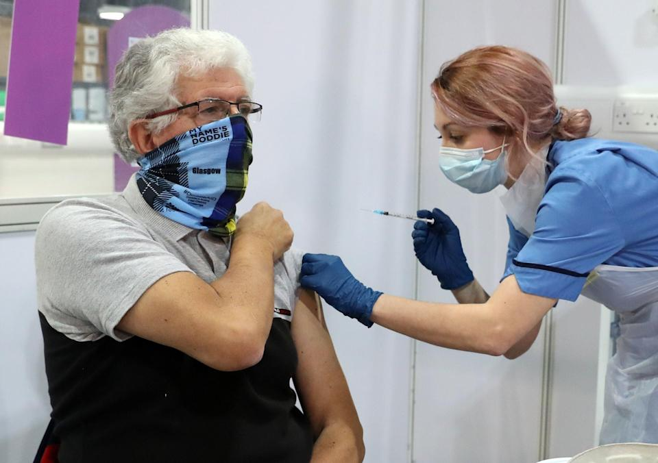 John Loch, 69, receives his Covid-19 vaccination from Nicole Clark at the NHS Louisa Jordan Hospital in Glasgow  (PA)