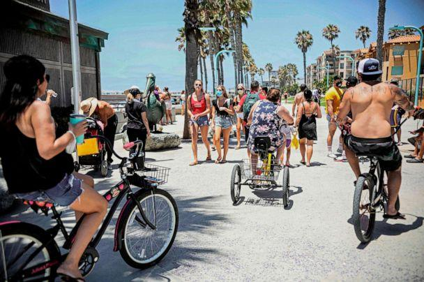 PHOTO: Beachgoers walk and ride along the boardwalk in the Pacific Beach area of San Diego, Calif., July 4, 2020, amid the coronavirus pandemic. (Sandy Huffaker/AFP via Getty Images)