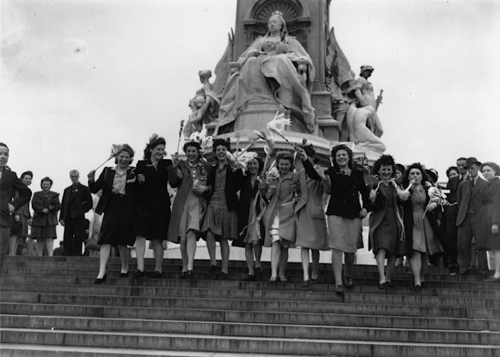 A group of London girls waving flags in front of the statue of Queen Victoria outside Buckingham Palace on VE Day, 8th May 1945. (Photo by Keystone/Hulton Archive/Getty Images)
