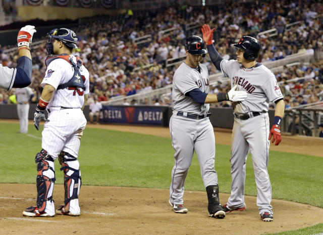 Cleveland Indians' Asdrubal Cabrera, right, congratulates Yan Gomes after Gomes' two-run home run off of Minnesota Twins pitcher Andrew Albers in the fourth inning of a baseball game, Thursday, Sept. 26, 2013, in Minneapolis. (AP Photo/Jim Mone)