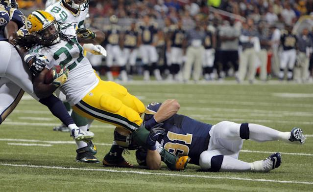 Green Bay Packers running back Eddie Lacy, left, struggles for yardage as St. Louis Rams defensive end Chris Long defends during the first quarter of an NFL preseason football game Saturday, Aug. 16, 2014, in St. Louis. (AP Photo/Scott Kane)