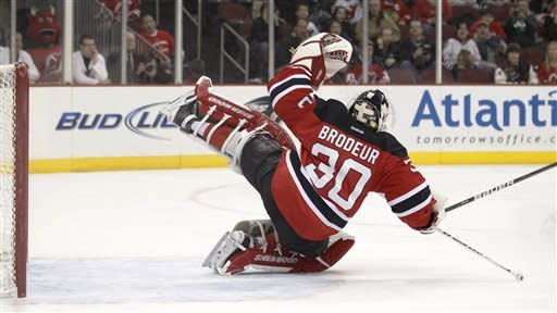 New Jersey Devils' Martin Brodeur deflects a shot by Chicago Blackhawks' Bryan Bickell, not pictured, in the first period of an NHL hockey game, Tuesday, March 27, 2012, in Newark, N.J. (AP Photo/Julio Cortez)