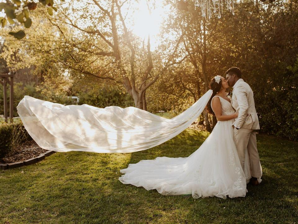 A bride and groom kiss in a field as the bride's veil flies up.