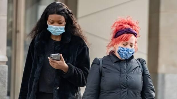 A pair of pedestrians wear masks on a warmer February day in Ottawa. (Brian Morris/CBC - image credit)