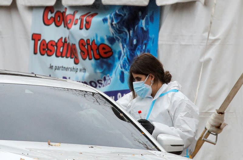 A healthcare worker takes a swab from a person sitting in a car at a drive-thru COVID-19 test center, during a surge in the coronavirus disease (COVID-19) infections in Newark, New Jersey