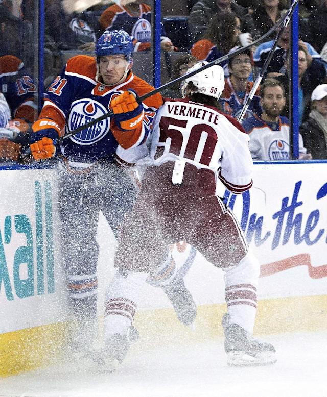 Phoenix Coyotes' Antoine Vermette (50) checks Edmonton Oilers' Andrew Ference (21) during the first period of an NHL hockey game Friday, Jan. 24, 2014, in Edmonton, Alberta. (AP Photo/The Canadian Press, Jason Franson)
