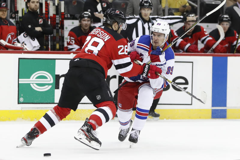 New Jersey Devils defenseman Damon Severson (28) keeps New York Rangers left wing Pavel Buchnevich (89) from the puck during the first period of an NHL hockey game Thursday, Oct. 17, 2019, in Newark, N.J. (AP Photo/Kathy Willens)