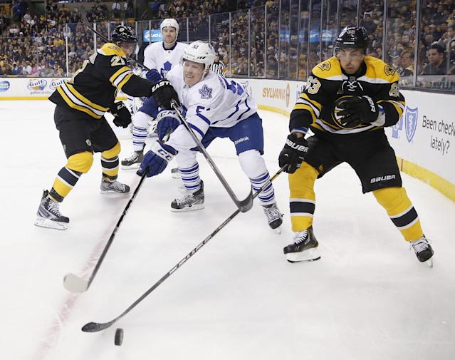 Toronto Maple Leafs' Jake Gardiner (51) battles Boston Bruins' Loui Eriksson (21), of Sweden, and Brad Marchand (63) for the puck in the second period of an NHL hockey game in Boston, Saturday, Nov. 9, 2013. (AP Photo/Michael Dwyer)