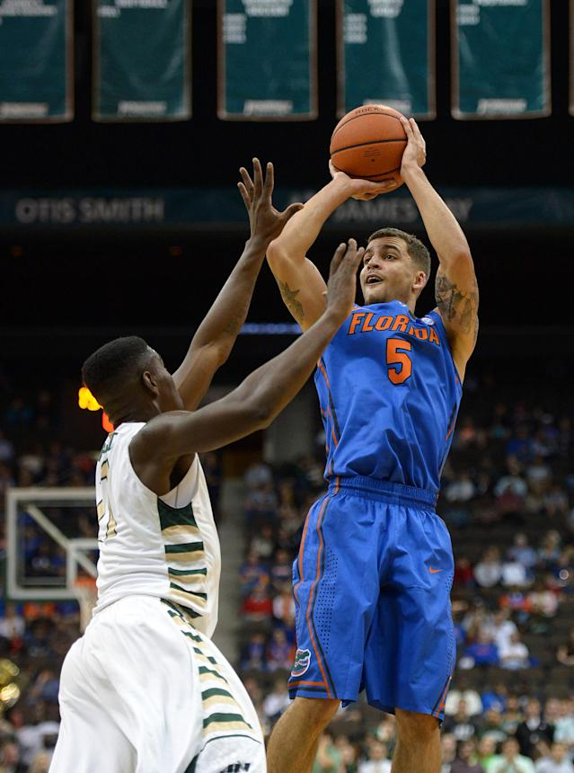 Florida guard Scottie Wilbikin (5) shoots while defended by Jacksonville guard Keith McDougald during the first half of an NCAA college basketball game, Monday, Nov. 25, 2013, in Jacksonville, Fla. (AP Photo/Jake Roth)