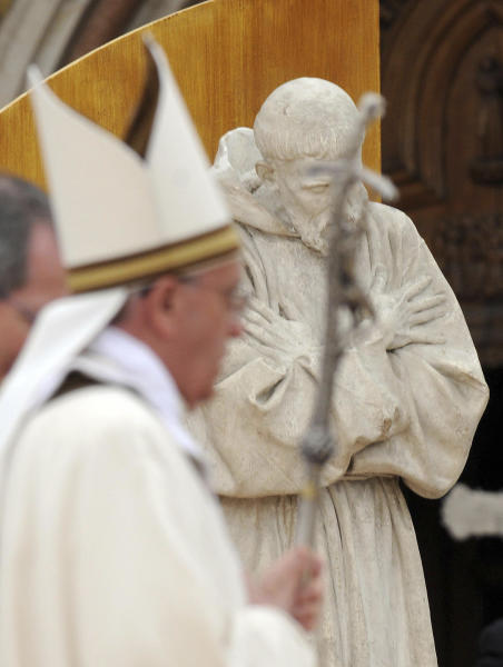 """Pope Francis passes by a statue of St. Francis as he walks with his pastoral staff during a mass, in Assisi, Italy, Friday, Oct. 4, 2013. Pope Francis made a pilgrimage Friday to the hillside town of Assisi and the tomb of his namesake, St. Francis, the 13th-century friar who renounced a wealthy, dissolute lifestyle to embrace a life of poverty and minister to the most destitute. St. Francis was famously told by God to """"repair my house."""" (AP Photo/Pietro Crocchioni, Pool)"""