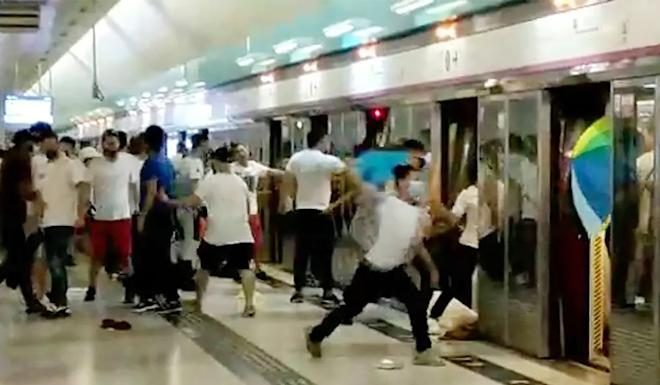 A group of white-clad men indiscriminately attack passengers and protesters at Yuen Long MTR station, with the police response time later criticised. Photo: Handout