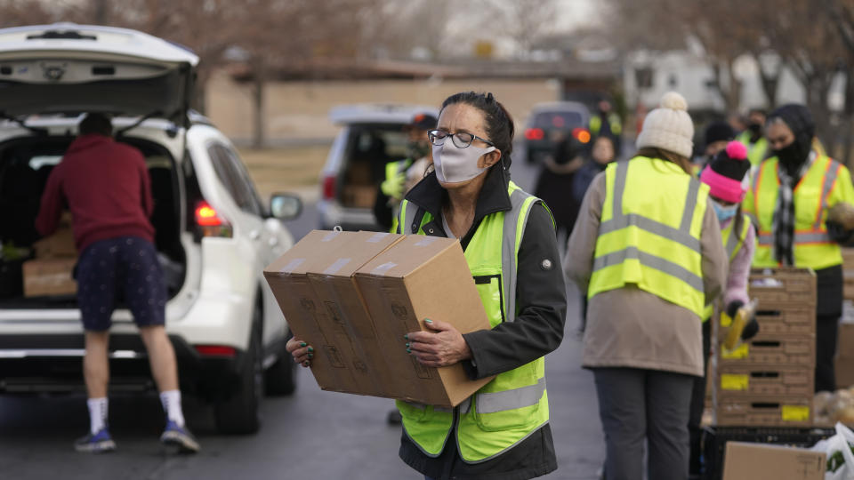 A volunteer carries food to waiting cars at the Utah Food Bank's mobile food pantry Thursday, March 11, 2021, in West Valley City, Utah. Since the coronavirus pandemic began many have relied more on food banks to get enough to eat. (AP Photo/Rick Bowmer)