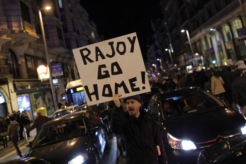 "Protestors shout slogans as they carry banners reading, ""Rajoy go home"" during a demonstration against corruption in Madrid, Spain, Saturday, Feb. 2, 2013. Spain's governing Popular Party insists its financial accounts are totally legal and denies a newspaper report of regular under-the-table payments to leading members, including current Prime Minister Mariano Rajoy. The scandal first broke when after the National Court reported that former party treasurer Luis Barcenas amassed an unexplained euro 22 million ($30 million) in a Swiss bank account several years ago. In a statement Thursday Jan. 31, 2013, the party denied the existence of ""hidden accounts"" or ""the systematic payment to certain people of money other than their monthly wages"". Spain's top prosecutor says there is sufficient cause to investigate fresh allegations of irregular financing of Spain's governing Popular Party and that if necessary Prime Minister Mariano Rajoy would be called in for questioning. (AP Photo/Andres Kudacki)"
