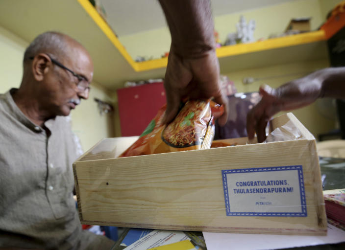 Officials of a Hindu temple open a box full of packaged food and sweets sent by a non-government organization to be distributed among villagers ahead of the inauguration of U.S. Vice President-elect Kamala Harris, in Thulasendrapuram, the hometown of Harris' maternal grandfather, south of Chennai, Tamil Nadu state, India, Tuesday, Jan. 19, 2021. The inauguration of President-elect Joe Biden and Vice President-elect Kamala Harris is scheduled be held Wednesday. (AP Photo/Aijaz Rahi)
