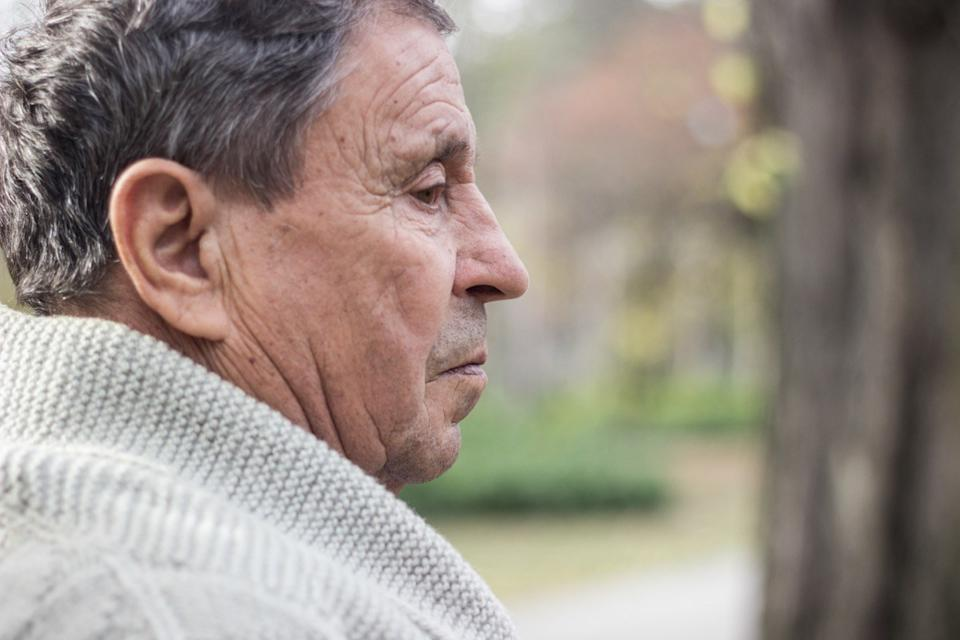 Portrait of a pensive senior man sitting on the bench, in the public park, outdoors. Old man relaxing outdoors and looking away. Portrait of senior man looking thoughtful