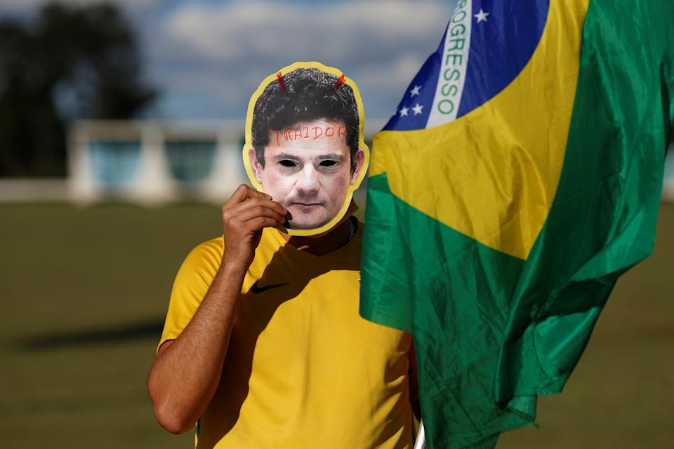 """A supporter of Brazil's President Jair Bolsonaro wears a mask that reads """"traitor"""" with the image of the former Brazil's justice Minister Sergio Moro in front of the Alvorada Palace, amid the coronavirus disease (COVID-19) outbreak, in Brasilia, Brazil, April 26, 2020. REUTERS/Adriano Machado"""