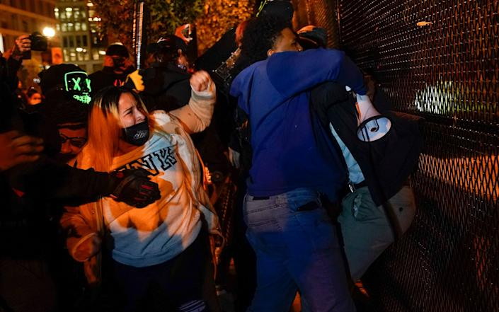Black Lives Matter supporters, left, clash with Trump supporters, obscured, after being taunted by the Trump supporters Tuesday, Nov. 3, 2020, in Washington - AP