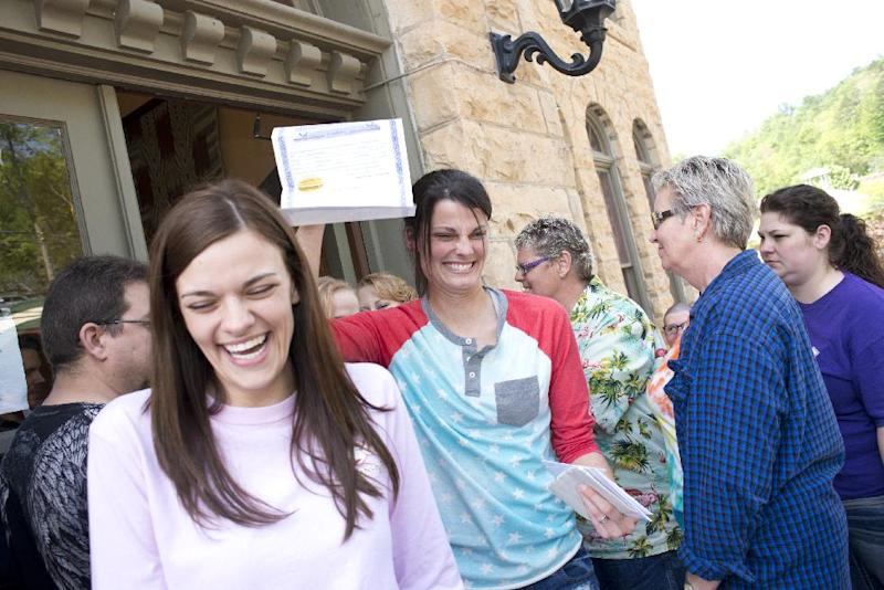 Kristin Seaton, center, of Jacksonville, Ark., holds up her marriage license as she leaves the Carroll County Courthouse in Eureka Springs, Ark., with her partner, Jennifer Rambo, left, of Fort Smith, Ark. Saturday, May 10, 2014, in Eureka Springs, Ark. Rambo and Seaton were the first same-sex couple to be granted a marriage license in Eureka Springs after a judge overturned Amendment 83, which banned same-sex marriage in the state of Arkansas. (AP Photo/Sarah Bentham)