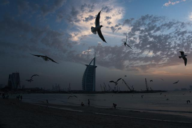 Seagulls soar over those gathered on a beach in front of the luxury Burj Al Arab hotel despite the global new coronavirus pandemic in Dubai, United Arab Emirates, Friday, March 20, 2020. The United Arab Emirates has closed its borders to foreigners, including those with residency visas, over the coronavirus outbreak, but has yet to shut down public beaches and other locations over the virus. (AP Photo/Jon Gambrell)