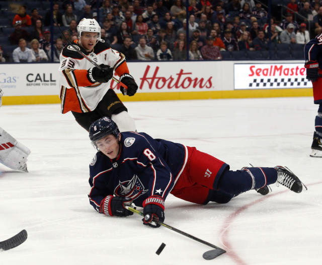 Columbus Blue Jackets defenseman Zach Werenski, bottom, reaches for the puck in front of Anaheim Ducks forward Jakob Silfverberg, of Sweden, during the first period of an NHL hockey game in Columbus, Ohio, Friday, Oct. 11, 2019. (AP Photo/Paul Vernon)