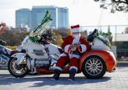 A man dressed in Santa Claus costume wearing a protective face mask pauses before Xmas Toy Run parade amid the coronavirus disease (COVID-19) outbreak, in Tokyo
