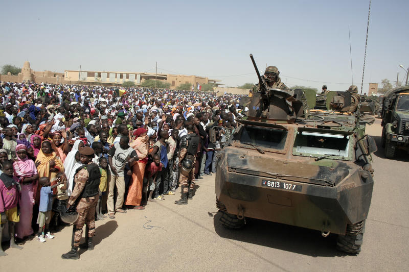 A French armored personal carrier drives past thousands who gathered to greet French President Francois Hollande on his visit to Timbuktu, Mali, Saturday Feb. 2, 2013, making a triumphant stop six days after French forces parachuted into Timbuktu to liberate the fabled city from the radical Islamists occupying it.(AP Photo/Harouna Traore)