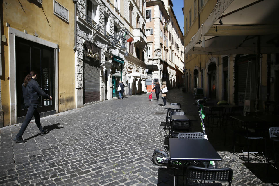 People walk in an empty street in downtown Rome, Monday, March 15, 2021. Half of Italy's regions have gone into the strictest form of lockdown in a bid to curb the latest spike in coronavirus infections that have brought COVID-19 hospital admissions beyond manageable thresholds. (Cecilia Fabiano/LaPresse via AP)