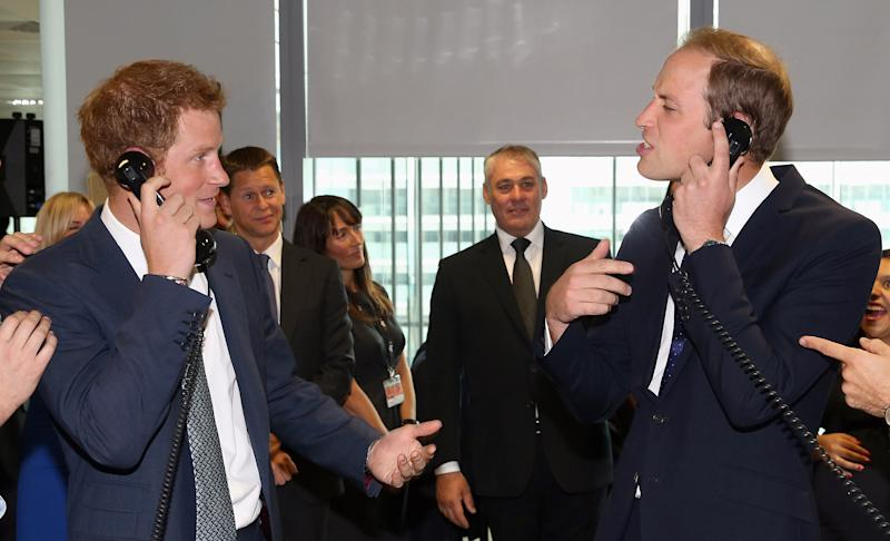 """Britain's Prince William, Duke of Cambridge, right and his brother Prince Harry take part in a trade on the BGC Partners trading floor, during the BGC Charity Day 2013, in Canary Wharf, London, Wednesday, Sept. 11, 2013. Prince William and Prince Harry have turned temporary stock traders, participating in a charity event in memory of victims of the Sept. 11 attacks. Assisted by professional traders, the royals took to the phones for an hour to broker deals, including one valued at 25 billion euros ($33 billion). They also found time to joke around, with Harry accusing his elder brother, father of 2-month-old Prince George, of indulging in """"baby chat"""" rather than sealing the deal. (AP Photo/ Chris Jackson, Pool)"""